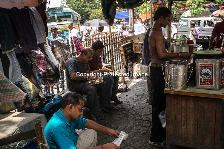 Customers sit to eat lunch at a make shift street food stall in BBD Bagh in Kolkata, West Bengal  on Friday, May 26, 2017. Photographer: Sanjit Das