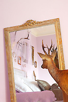 Auguste, the stuffed antique stag, gazes into a gilt-framed mirror where a 1940s mirrored headboard can be seen surrounded by an eclectic collection of picture frames