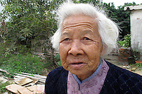 20120117 CHINA GUANGDONG PROVINCE : An old woman is seen in a small village next to Hallstatt, China's copy of the Austrian alpine town of the same name, Boluo Township, Huizhou City, Guangdong Province, China, 17 January 2012. Property developments such as this are expected to run into financial difficulites in 2012 as the Chinese economy and property market continue to cool, in reaction to the ongoing sovereign debt crisis in Europe.<br /> SINOPIX / ALEX HOFFORD