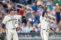 Michigan Wolverines pitcher Tommy Henry (47) points with teammate Blake Nelson toward Jordan Brewer after throwing out a runner at third against the Vanderbilt Commodores during Game 1 of the NCAA College World Series Finals on June 24, 2019 at TD Ameritrade Park in Omaha, Nebraska. Michigan defeated Vanderbilt 7-4. (Andrew Woolley/Four Seam Images)