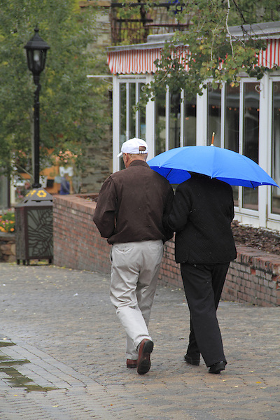 Elderly couple walking in the rain, Vail Village, Colorado.