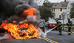 MANASQUAN, NJ — April 1, 2016 — Manasquan firefighters Kevin McCredie and Tom Schofield get water on a 2000 Ford Focus that is fully engulfed in flames at about 9:40am on Broad Street, here. The driver of the vehicle, Nancy Trapani, was not injured.  photo by Andrew Mills