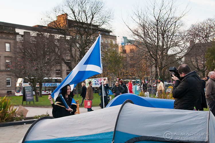 A tourists gets her picture taken with  a Scottish flag, at the Occupy Edinburgh camp.