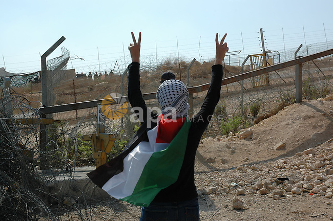 Palestinian protestor waves with V during a demonstration against Israel's separation barrier in the West Bank village Bilin near Ramallah on Oct 9, 2009. Photo by Nedal Shtieh