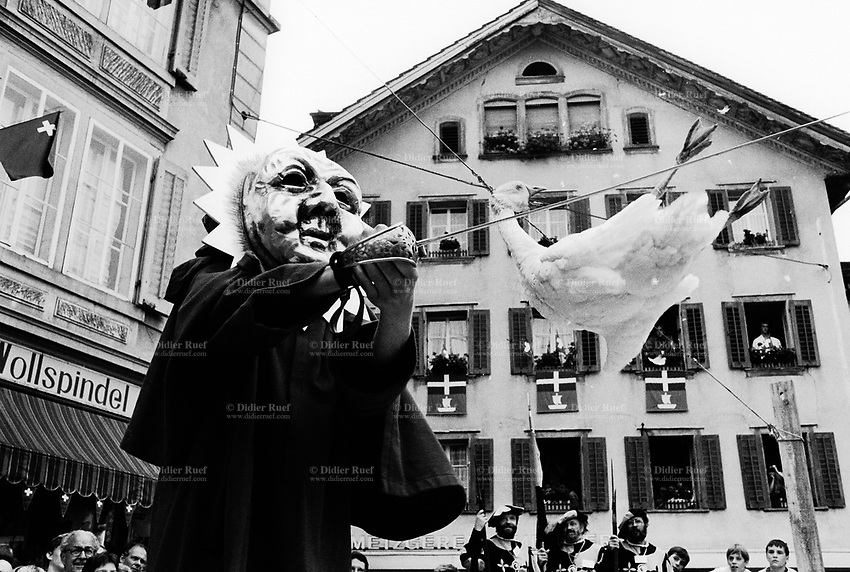 """Switzerland. Canton Schwyz. Brunnen. Crowd during the Swiss costum's fair. The people are watching the old traditional habit from """"Gansabhauet Sursee"""": a man or a woman have to drink a glass of wine, wear a sun helmet on the head and face, be turned around, then try to cut the goose's neck with one saber's thrust. The animal is tied on a rope. Swiss flag. © 1991 Didier Ruef"""