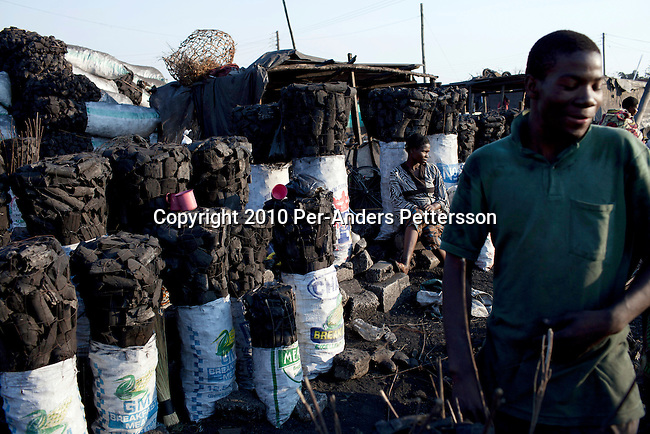 LUSAKA, ZAMBIA - JUNE 17: People work in a charcoal market on June 17, 2010 in central Lusaka, Zambia. Many people in Zambia uses charcoal for cooking. Cook stoves are supplied by (CDM) Clean Development Mechanism. CDM is one of the mechanisms in article 12 in the Kyoto Protocol that allows industrial nations to meet their CO 2 emission reduction targets by investment and transfer of sustainable technologies in development countries. In Zambia, Lusaka Sustainable Energy project , is providing house-holds with cook stoves, financed by RWE Power AG, the German power utility. The project in Zambia seeks to switch charcoal consuming households to sustainable harvested sticks of wood used for the cookers, and by doing that saving trees and the environment in Zambia. House-holds are save a substantial amount of money every month by not buying charcoal, which usually is a major cost for poor people in the country. (Photo by Per-Anders Pettersson/Getty Images