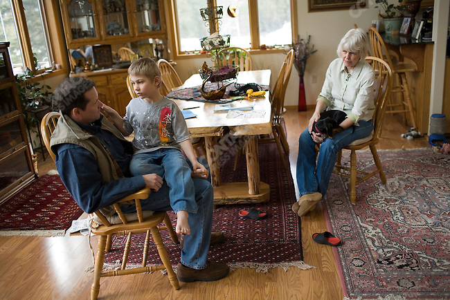 Stuart Walsh visits his son, Johnny, who is enrolled at the Ranch for Kids, a therapeutic boarding school located near Eureka, Montana for adopted foreign children who are experiencing difficulties, such as adoption disruption, with their new U.S. families. Johnny currently lives with Joyce Sterkel (right), the founder of the ranch. Montana, March 1, 2008.