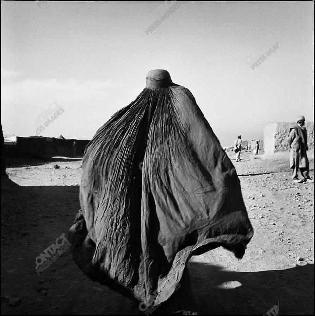 An Afghan woman refugee walks through Shamsatoo Refugee Camp near Peshawar, Pakistan, January 2001