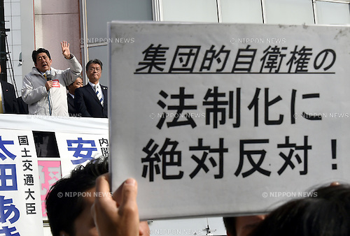 Decem ber 7, 2014, Tokyo, Japan - A protester holds a placard opposing legistlation of collective self-defense rigt during Japan's Prime Minister Shinzo Abe's stumping stop in the capital's 12th precinct on Sunday, December 7, 2014. Abe's ruling Liberal Democratic Party is expected to retain its dominance in the December 14 parliament's lower house election, according to a latest polls, according to latest polls. (Photo by Natsuki Sakai/AFLO) AYF -mis-