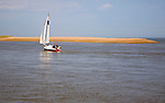 Sailing boat at the mouth of the River Ore at the tip of Orford Ness shingle spit, North Weir Point, Shingle Street, Hollesley, Suffolk, England