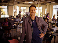 An office manager stands in front of his newly redesigned workspace with his team working hard behind him