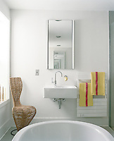A pair of mirrors appears to stretch to infinity above the wash basin in this cool and tranquil bathroom