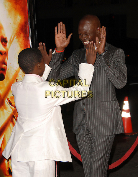 CARUSO KUYPERS & DJIMON HOUNSOU.The Warner Brothers Pictures Premiere of Blood Diamond held at The Grauman's Chinese Theater in Hollywood, California, USA. .November 6th, 2006.half length hands palms gesture white suit jacket grey gray pinstripe wearing Gucci.CAP/DVS.©Debbie VanStory/Capital Pictures