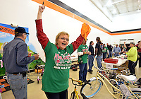 STAFF PHOTO BEN GOFF  @NWABenGoff -- 12/03/14 Iris Beal leads a cheer as as dozens of volunteers assemble and quality check nearly 300 donated bicycles and tricycles in preparation for the NWA United Toys for Joy Christmas Toy Run at Pig Trail Harley-Davidson in Rogers on Wednesday Dec. 3, 2014. Hundreds of bikers will ride from Pig Trail Harley-Davidson to the Benton County Fairgrounds with the bicycles and toys on Dec. 13.