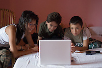 Three children lying on a bed using a laptop, France.