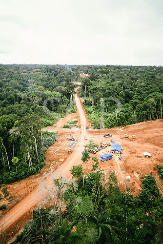 Amazonas, Brazil. Aerial view of rainforest being cleared for oil exploration, a new road with a line of trucks and a new bridge, bulldozers. Amazon.