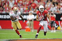 Sept. 13, 2009; Glendale, AZ, USA; Arizona Cardinals wide receiver (11) Larry Fitzgerald runs the ball as San Francisco 49ers cornerback (22) Nate Clements chases in the first quarter at University of Phoenix Stadium. Mandatory Credit: Mark J. Rebilas-