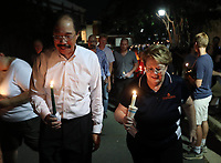 UVa president Teresa Sullivan, right, walks with thousands of UVa students, faculty and Charlottesville residents in a candle light march across grounds Wednesday night in Charlottesville, Va. The march was an effort to stomp out the hate across campus from last Friday's torch march. Photo/Andrew Shurtleff