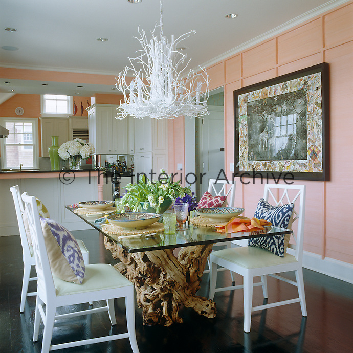 The black wooden floor highlights the white dining chairs and chandelier and the dining table is built around a 400-pound grapevine trunk