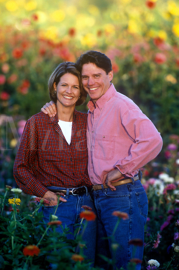 Middle age couple embrace in their country flower garden.