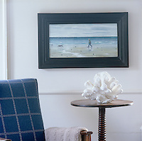Close up of white coral on a pedestal table with a sea scene hanging on the wall behind