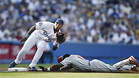 Adrian Beltre of the Los Angeles Dodgers waits for the ball as Jimmy Rollins of the Philadelphia Phillies slides into third base during a 2002 MLB season game at Dodger Stadium, in Los Angeles, California. (Larry Goren/Four Seam Images)