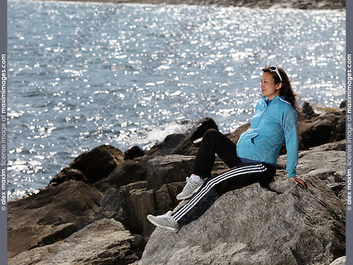 Pregnant young woman sitting at a rocky shore near water