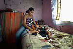 Feride Ramadan comforts her one-year old son Birdzhan in their house in the Maxsuda neighborhood of Varna, Bulgaria. They are Turkish-speaking Roma, and were violently driven out of one neighborhood by racist gangs. They took refuge in a United Methodist Church for a year before finding this small house to rent.