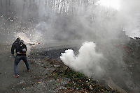 Skouries, Greece Sunday 23 November 2014<br /> Pictured: A protester throws a pyrotechnic towards the riot police officers<br /> Re: Riot police called to break up a protest by local residents against a Canadian-run goldmine in Skouries, in the Chalkidiki area. Eldorado firm has been accused of dumping toxic waste generated during gold processing in northern Greece, into local rivers. Teargas was used by the police to disperse the protesters who retaliated with pyrotechnics.