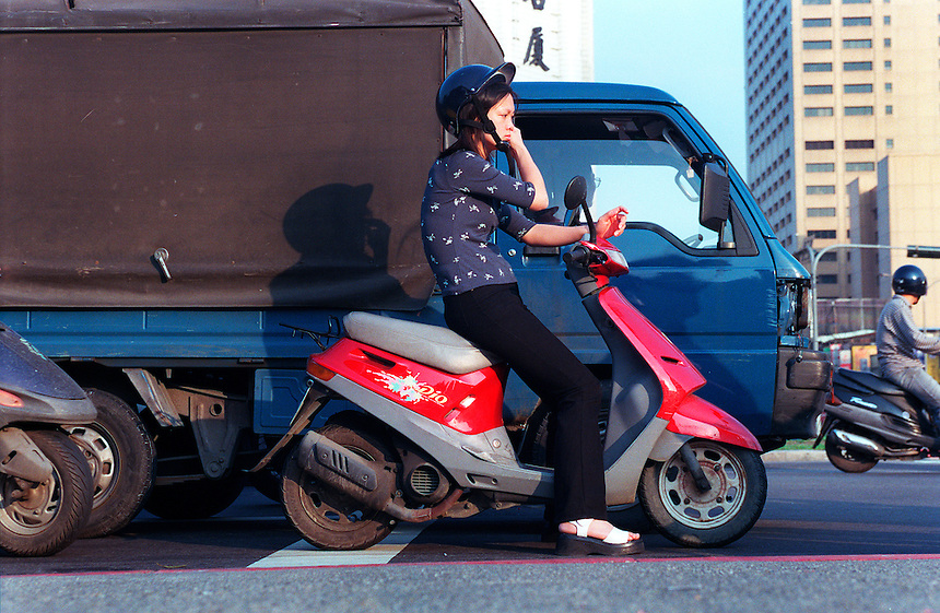 A woman on a scooter stops in traffic on a street in Taipei, Taiwan.
