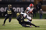 Emeka Emezie (86) of the North Carolina State Wolfpack is tackled by Ja'Sir Taylor (24) of the Wake Forest Demon Deacons during second half action at BB&T Field on November 18, 2017 in Winston-Salem, North Carolina.  The Demon Deacons defeated the Wolfpack 30-24.  (Brian Westerholt/Sports On Film)