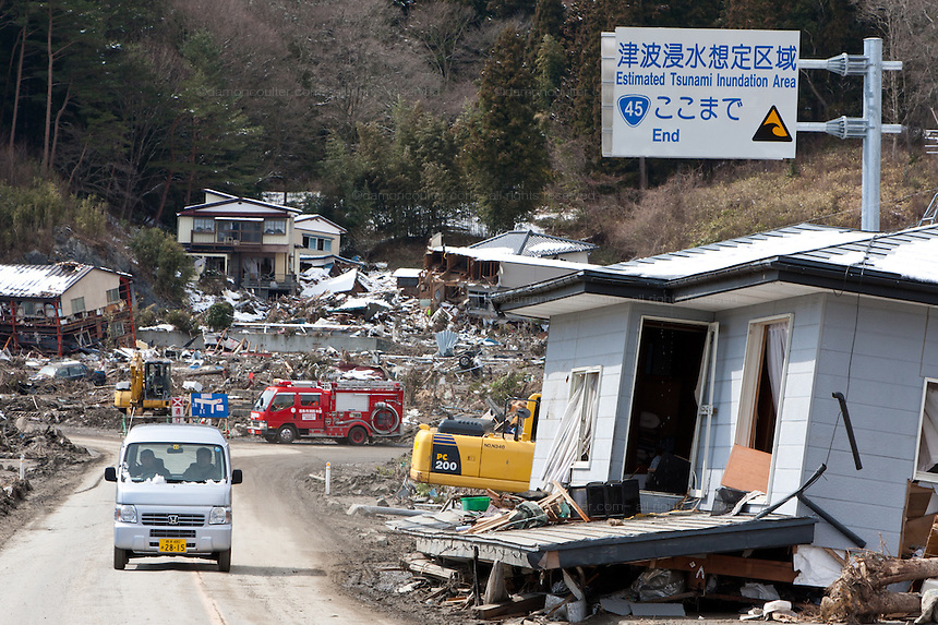 A sign warning about tsunamis above a ruined house after the tsunami that struck the north east coast of Japan on March 11th in Otsuchi, Iwate, Japan. March 17th 2011