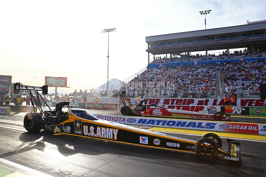 Oct 31, 2014; Las Vegas, NV, USA; NHRA top fuel driver Tony Schumacher (near) races alongside Doug Kalitta during qualifying for the Toyota Nationals at The Strip at Las Vegas Motor Speedway. Mandatory Credit: Mark J. Rebilas-USA TODAY Sports