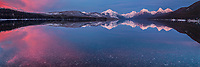 A Pink sunset and mirror calm water on Lake McDonald in Winter.  Glacier Nat'l Park.