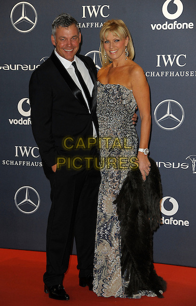 Darren Clarke & guest.Arrivals at the Laureus 2012 World Sports Awards held at the Queen Elizabeth II Centre, London, England..February 6th, 2012.full length black suit grey gray strapless dress print.CAP/CAS.©Bob Cass/Capital Pictures.