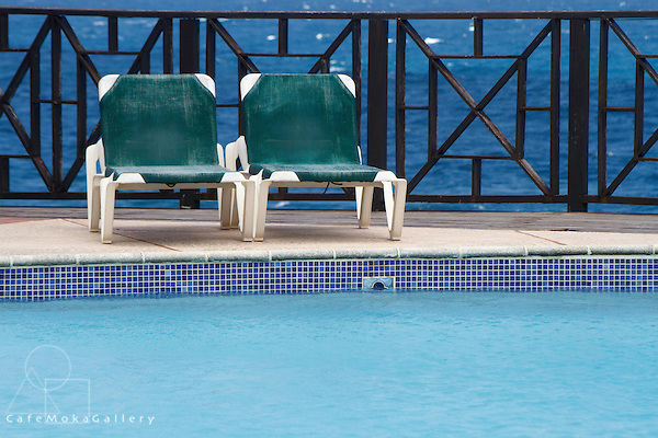 Barbados - Two sunbeds by a turquoise pool with Caribbean style fence and blue sea in the background