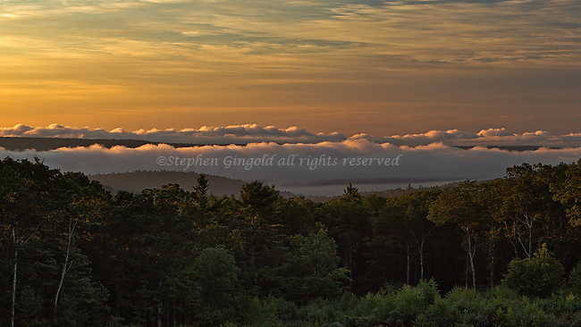 Just after sunrise, warm light illuminates the tops of heavy clouds sitting over the Quabbin Reservoir as seen from the Route 202 overlook in Pelham, Massachusetts.