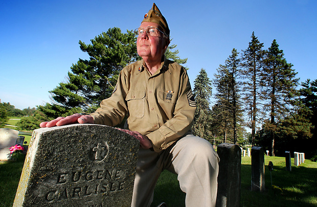 Gerald LeBlanc, a tireless advocate for the maintenance and repair of veterans' headstones, kneels with a row of aging Worls War I grave markers at Glendale Cemetery in Des Moines, Iowa.