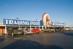 Trading Post Restaurant with an Indian with feather headdress watching over the parked cars near Clinton, Okla.
