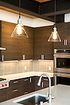 Glass pendants hang over an island in a contemporary kitchen. This image is available through an alternate architectural stock image agency, Collinstock located here: http://www.collinstock.com