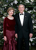 "United States President George W. Bush and first lady Laura Bush pose for their Official Holiday Portrait near the White House Christmas tree in the Blue Room of the White House in Washington, D.C. on December 4, 2005.  In keeping with this year's theme, ""All Things Bright and Beautiful!"" the Fraser fir is decorated with fresh white lilies.<br /> Mandatory Credit: Eric Draper - White House via CNP"