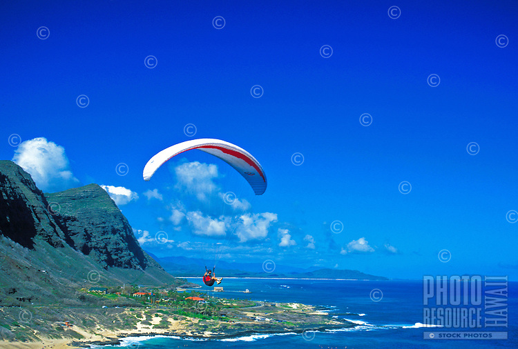 A paraglider enjoys riding the warm updrafts over Makapuu Beach Park on Oahu's windward side. This view is from Makapuu point.