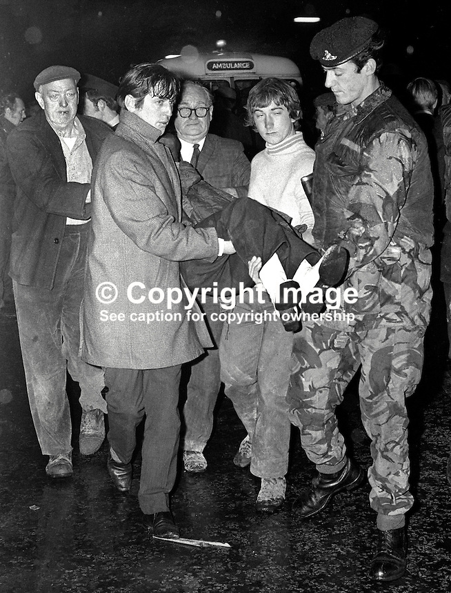 Civilians and a soldier carry an injured man from the wreckage of the Red Lion pub on the Ormeau Road, Belfast, N Ireland, on 2nd November 1971. Three men died in the Provisional IRA bombing. The bar was beside Ballynafeigh RUC station. 197111020430a.<br />