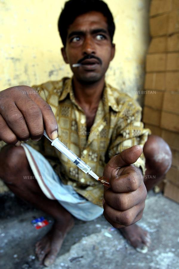 2005. Bangladesh, Dhaka. A man injects himself pathedrine, a widely available pain-killer used as a drug...2005. Bangladesh, Dhaka. Un homme s'injecte de la pathedrine, un anti douleur très repandu, utilisé en drogue..