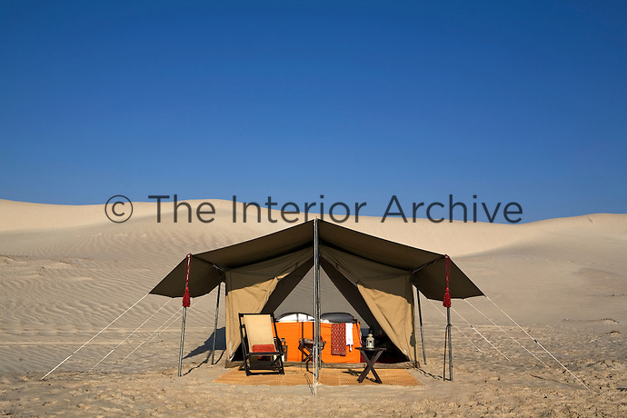 One of the camps sleeping tents on the beach against the backdrop of a clear blue sky and sand dunes