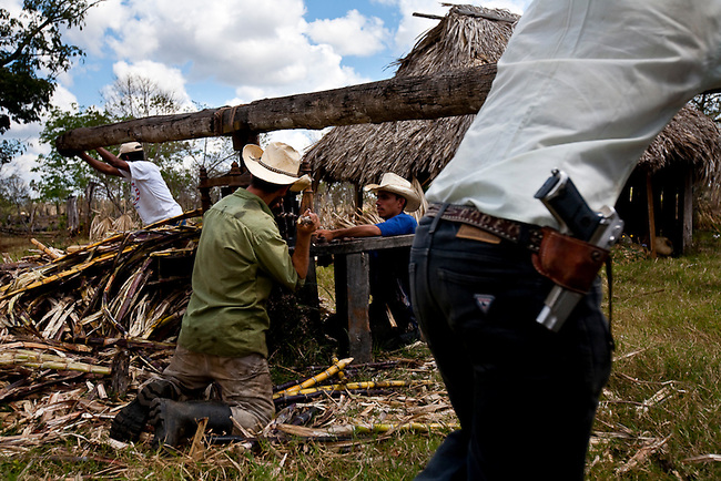 Ranchers squeeze sugar cane to make juice inside the Mayan Biosphere. Much of the reserve has become a wild west, where the settlers must protect and take care of themselves with no help from the government.