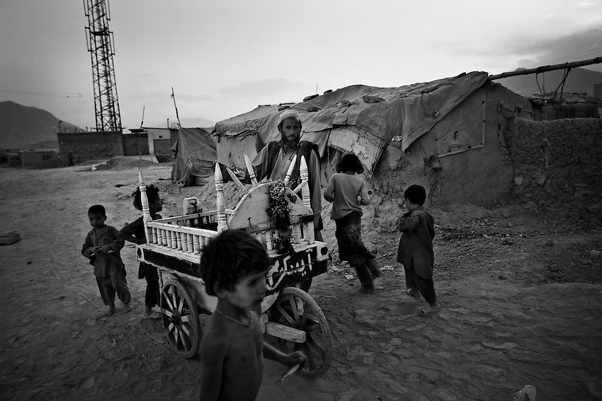 Displaced Afghan children gather around an ice cream vendor in Chamane Babrak, a tented slum community for displaced Afghans just west of Kabul, Afghanistan, Monday, Oct 5, 2009. The majority of the familes in Chamane Babrak are returnees from Iran.