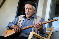 Munzur Valley, Turkey - July, 17, 2014 - Zeynal Batar, the dede (Alevi religious leader) of Kedek village, plays the cura while singing an emotional  dirge. CREDIT: Michael Benanav for The New York Times