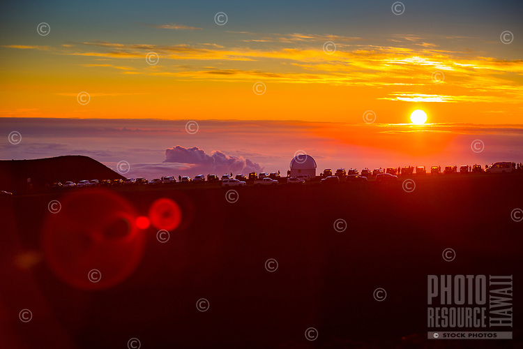 A line of cars with spectators taking in a fiery sunset are parked around an observatory  on Mauna Kea, Big Island.