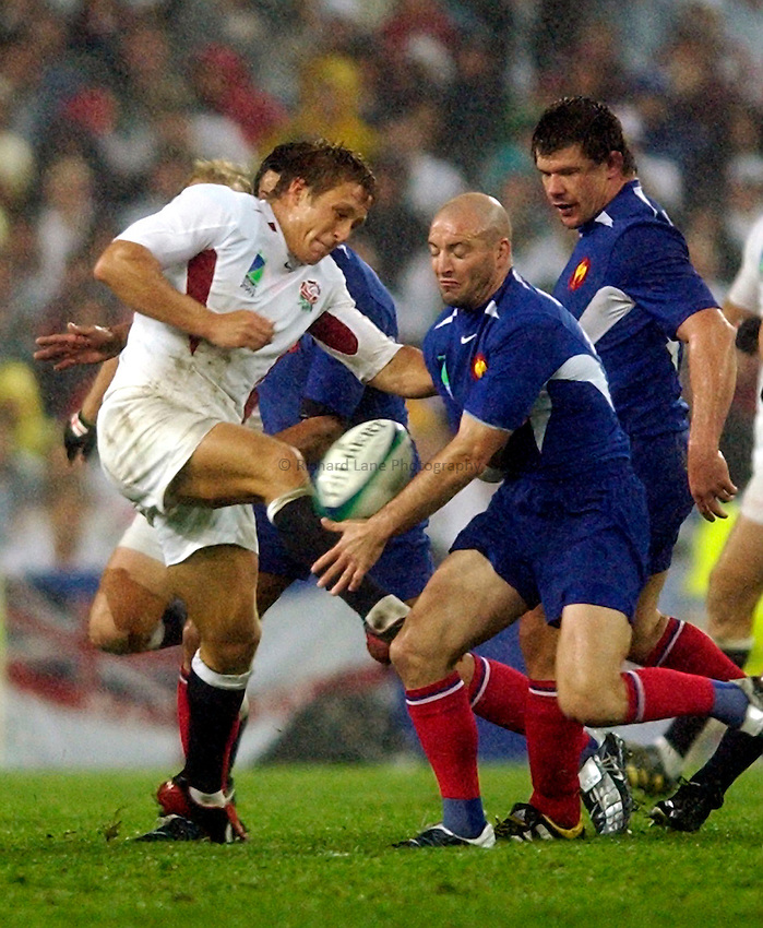Photo. Richard Lane. .France v England. Semi-final at the Telstra Stadium, Sydney. RWC 2003..16/11/2003..England's Jonny Wilkinson hacks the ball away as Gerald Merceron chellenges.